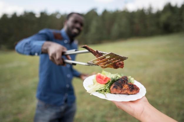 バーベキューのために人にステーキを与える男