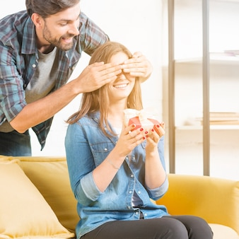 Man giving surprise gift to girlfriend covering her eyes