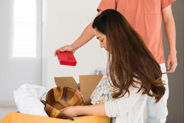 段ボール箱の開梱物の間にアジアの女性にサプライズギフトを与える男性。新しい家に引っ越した初日の妻へのサプライズプレゼント。新しいカップルの生活を始めましょう。