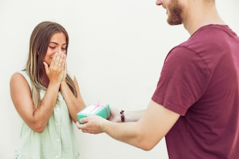 Man giving surprise gift to his amazed girlfriend