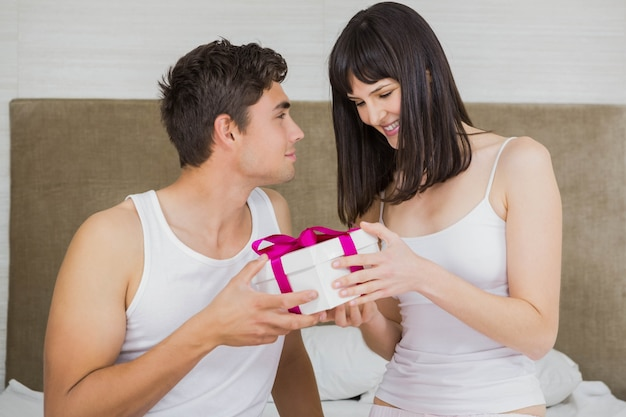 Man giving surprise gift to woman in bedroom