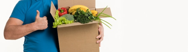 Человек дает большие пальцы и держит коробку с продуктами