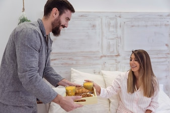 Man giving tray with romantic breakfast to woman