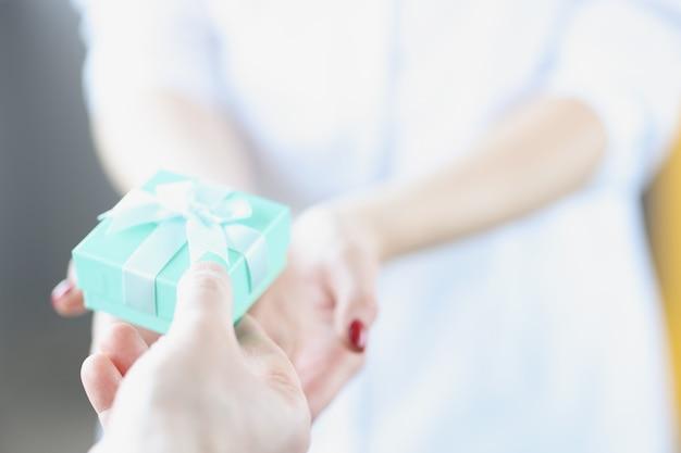 나비 근접 촬영 여자 파란색 선물 상자를 주는 남자. 사랑하는 사람을 위한 선물 선택 개념