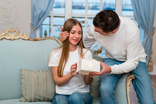 Man giving woman present on sofa