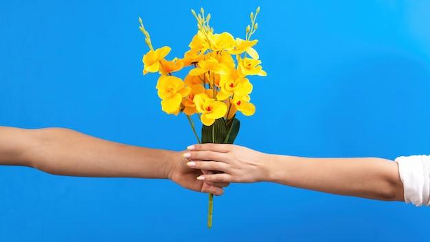 Мужчина дарит желтые цветы женщине