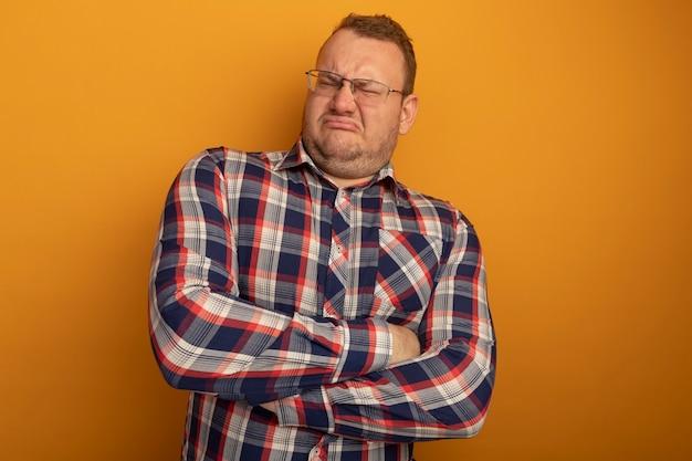 Uomo con gli occhiali e la camicia a quadri insoddisfatto del viso accigliato con le braccia incrociate in piedi sopra il muro arancione