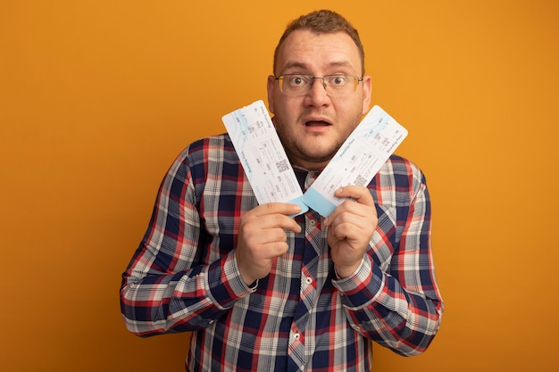 Man in glasses and checked shirt holding air tickets  surprised standing over orange wall