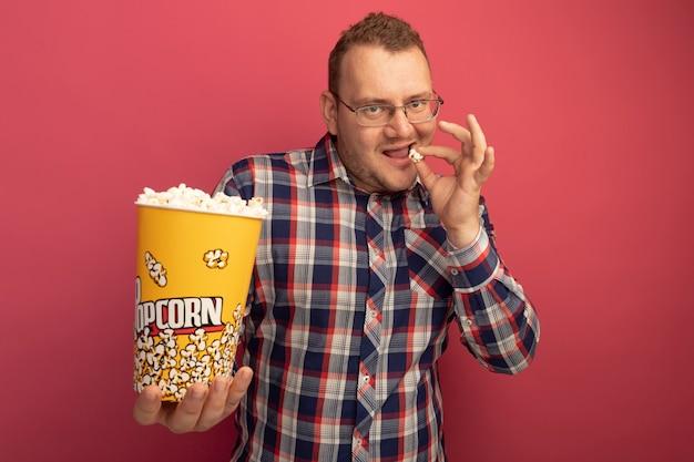 Uomo in bicchieri e camicia a quadri tenendo la benna con popcorn mangiare sorridente fiducioso in piedi oltre il muro rosa