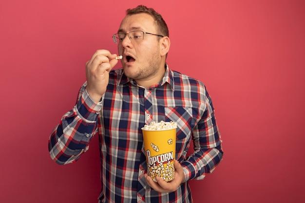 Uomo in bicchieri e camicia a quadri che tiene secchio con popcorn mangiare con piacere in piedi sopra il muro rosa