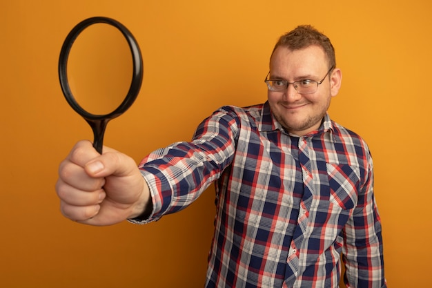 Man in glasses and checked shirt holding magnifying glass looking at it with smile on face standing over orange wall