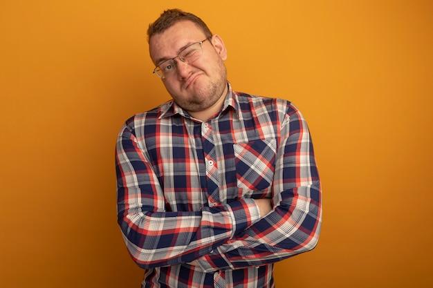 Uomo in bicchieri e camicia a quadri guardando da parte con espressione scettica rendendo la bocca ironica in piedi sopra la parete arancione