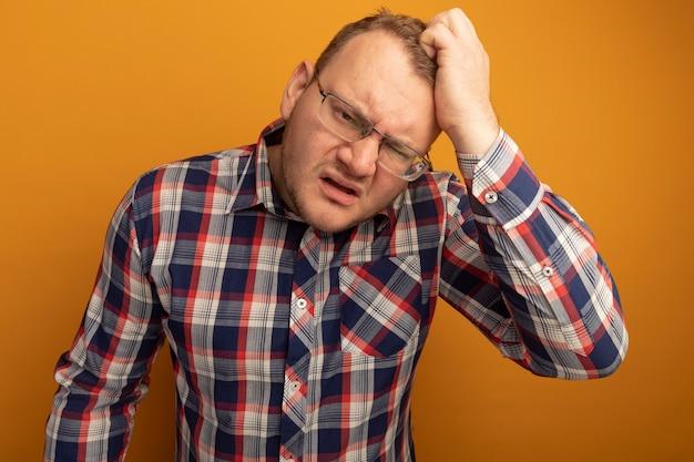 Uomo con gli occhiali e la camicia a quadri che sembra confuso e molto ansioso grattandosi la testa in piedi sopra il muro arancione