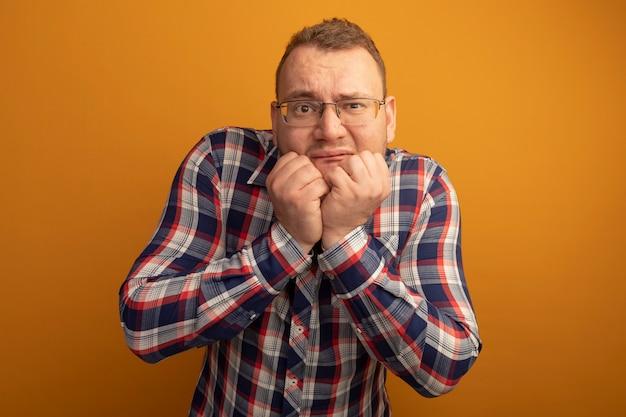 Uomo con gli occhiali e la camicia a quadri stressati e nervosi chiodi mordaci in piedi sopra la parete arancione