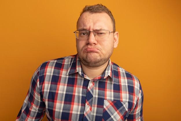 Uomo con gli occhiali e la camicia a quadri con la faccia accigliata dispiaciuta in piedi sopra il muro arancione