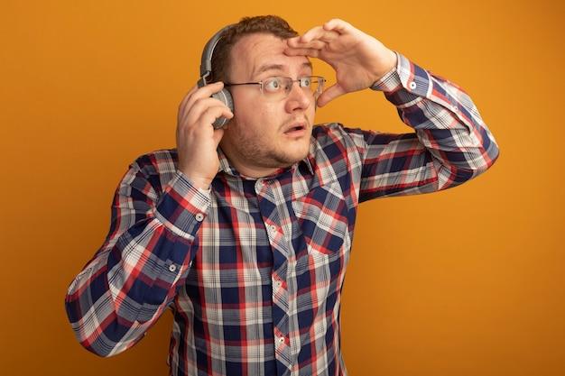 Uomo con gli occhiali e camicia a quadri con le cuffie che guarda lontano con la mano sopra la testa in piedi sopra la parete arancione