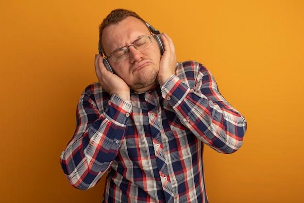 Uomo con gli occhiali e camicia a quadri con le cuffie con gli occhi chiusi godendo la sua musica preferita in piedi sopra la parete arancione