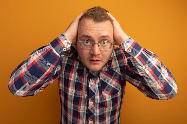 Uomo con gli occhiali e camicia a quadri preoccupato e confuso con le mani sulla testa in piedi sopra il muro arancione