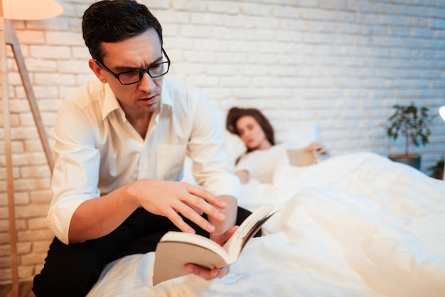 Man in glasses concentrated on reading book.