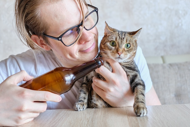 A man in glasses drinks alcohol beer hugging an animal cat at home.