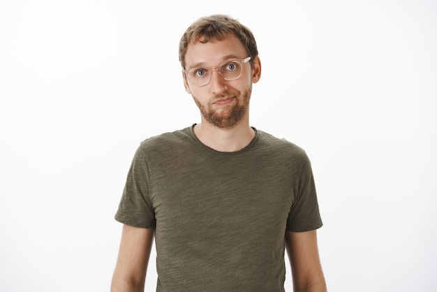 Man in glasses and green casual t-shirt smiling friendly standing relaxed and calm