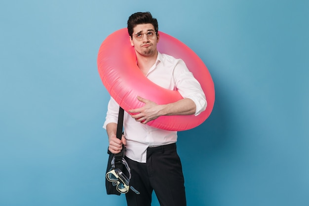 Man in glasses holds inflatable circle, diving mask and bag for documents. guy in office clothes posing on blue space.