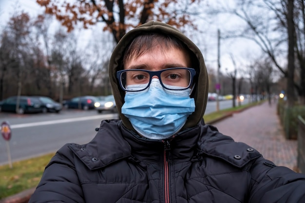 A man in glasses, medical mask, the hood and jacket at cloudy weather, looking into the camera, road on the background