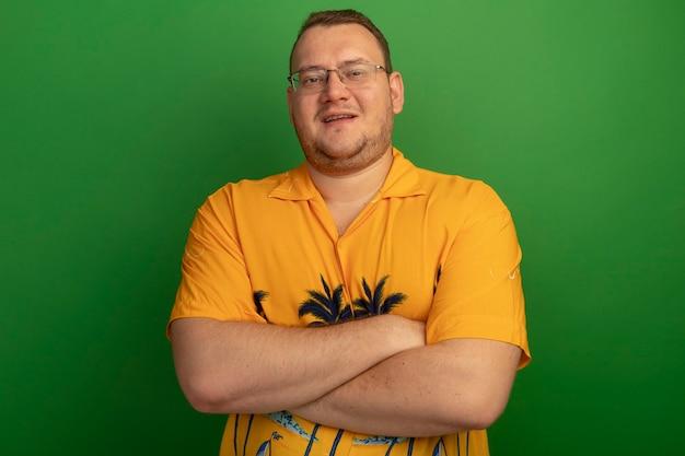 Uomo con gli occhiali e la maglietta arancione con il sorriso sul viso con le braccia incrociate in piedi sopra la parete verde