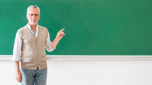 Man in glasses pointing at blackboard