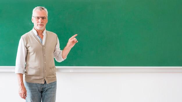 Man in glasses pointing at blackboard