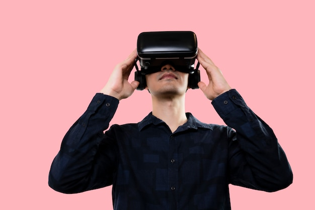 Man glasses of vr virtual reality headset is looking at interactive screen, pink isolated background.