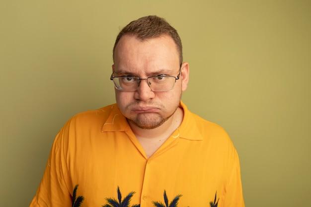 Uomo con gli occhiali che indossa una maglietta arancione che soffia sulle guance cercando dispiaciuto in piedi sopra la parete chiara