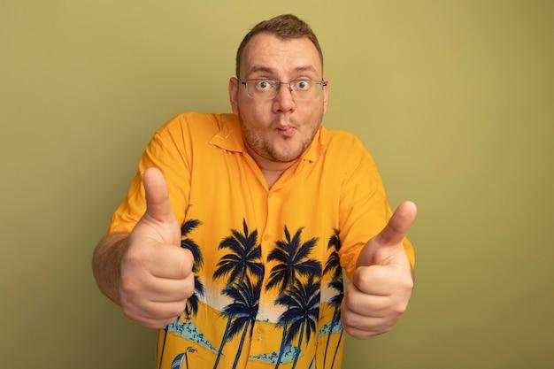 Uomo con gli occhiali che indossa la camicia arancione confuso che mostra i pollici in su in piedi sopra il muro di luce