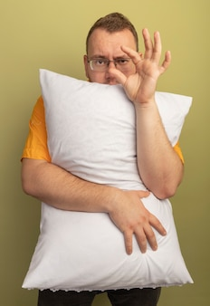 Man in glasses wearing orange shirt hugging pillow  showing small size gesture, symbol measure standing over light wall