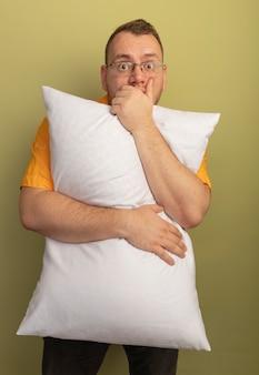 Uomo con gli occhiali che indossa la camicia arancione che abbraccia cuscino sorpreso che copre la bocca con la mano in piedi sopra la parete chiara