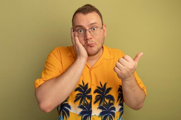 Uomo con gli occhiali che indossa una maglietta arancione che sembra confuso che mostra i pollici in su essendo confuso in piedi sopra la parete chiara