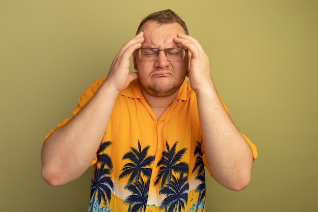 Uomo con gli occhiali che indossa una maglietta arancione alla ricerca di malessere toccando la testa con forte mal di testa in piedi sopra la parete verde