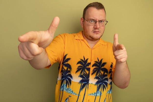 Uomo con gli occhiali che indossa la maglietta arancione che punta con il dito indice dispiaciuto in piedi sopra la parete chiara