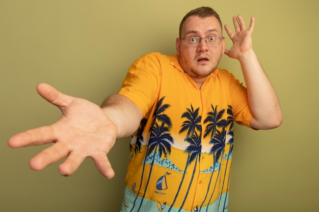 Uomo con gli occhiali che indossa una maglietta arancione spaventato tenendo le mani in piedi sopra la parete chiara