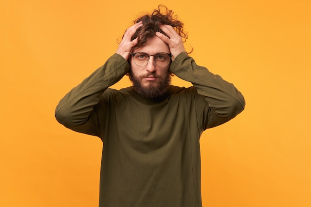 A man in glasses with a beard clutched at his head looks upset sad, got in desperate situations