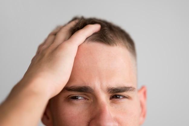 L'uomo scivolando le dita tra i capelli