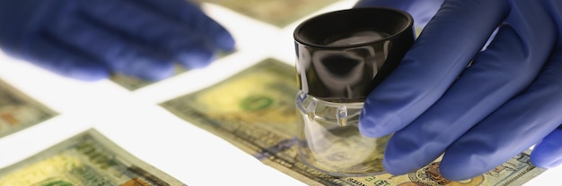 Man in gloves checking counterfeit money with magnifying glass closeup fake money concept