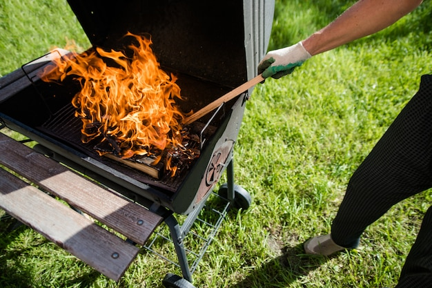 A man in gloves straightens burning wood in the grill. summer barbecue.