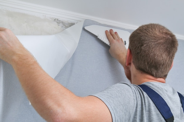 Man glues gray vinyl wallpaper on a non-woven backing. renovation of the room.