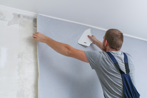 A man glues gray vinyl wallpaper on a non-woven backing. renovation of the room.
