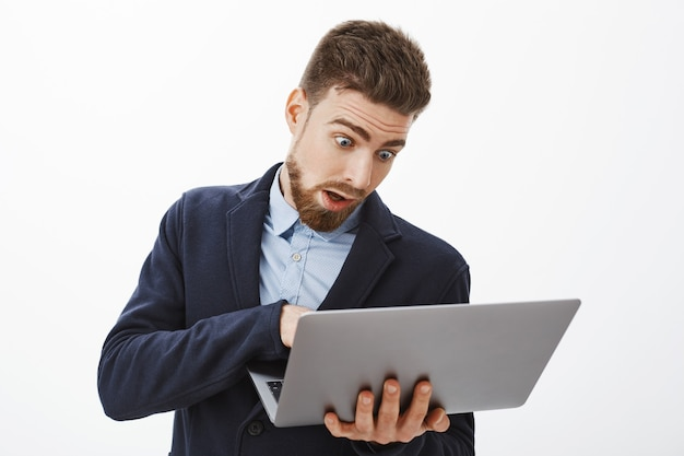 Man going crazy, being in rush working on project. anxious troubled good-looking male with beard in suit holding laptop looking at computer screen, posing concerned and focused against grey wall