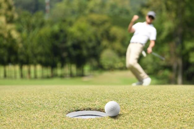 골프 녹색에 골프 공 후 응원하는 남자 골퍼