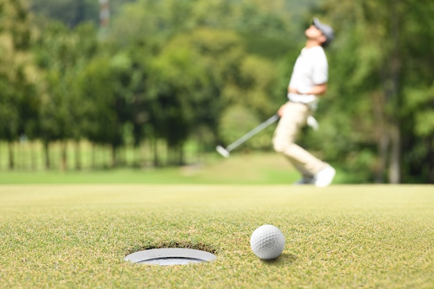 Человек гольфист аплодисменты после мяч для гольфа на зеленый гольф