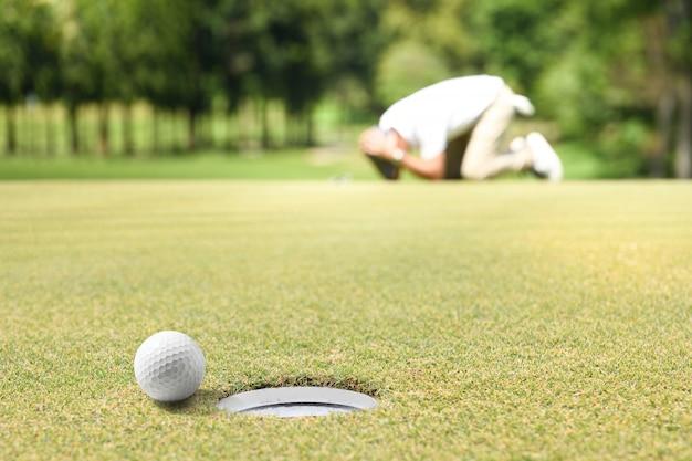 Человек-гольфист чувствует себя разочарованным после того, как мяч для гольфа в мяч попал в лунку