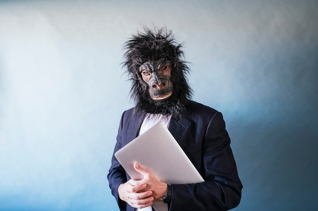 Man in gorilla mask with laptop under his arm
